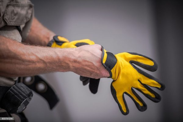 wearing-construction-safety-gloves-closeup-photo-caucasian-contractor-preparing-job-wearing-safety-gloves-100638723